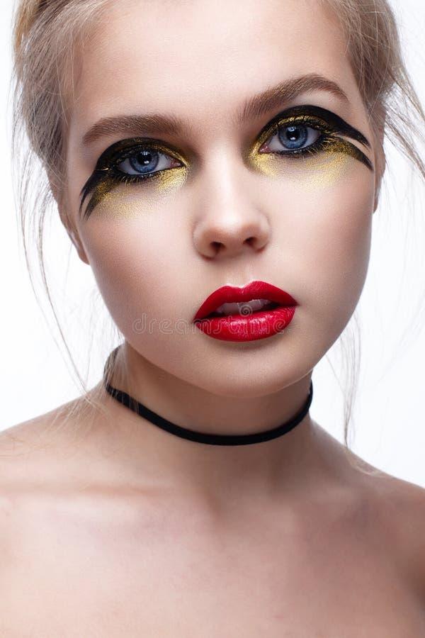 Junges Mädchen mit kreativem Schwarz- und Goldmake-up Schönes Modell mit einem Kontrolleur auf Hals und den Rotlippen Vollkommene stockfotos
