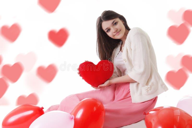 Junges Mädchen mit roten Ballonen auf Herz-förmigem bokeh lizenzfreie stockbilder