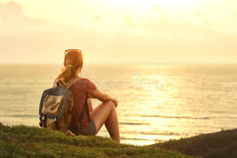Junges Mädchen mit Rucksack Sonnenuntergang genießend hörend Musik auf p stockbild