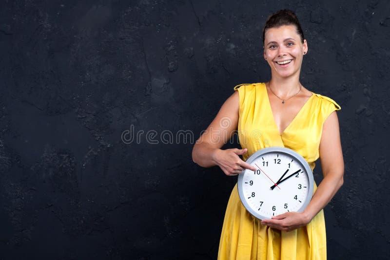 Junges Mädchen mit runden Uhren lizenzfreie stockfotografie