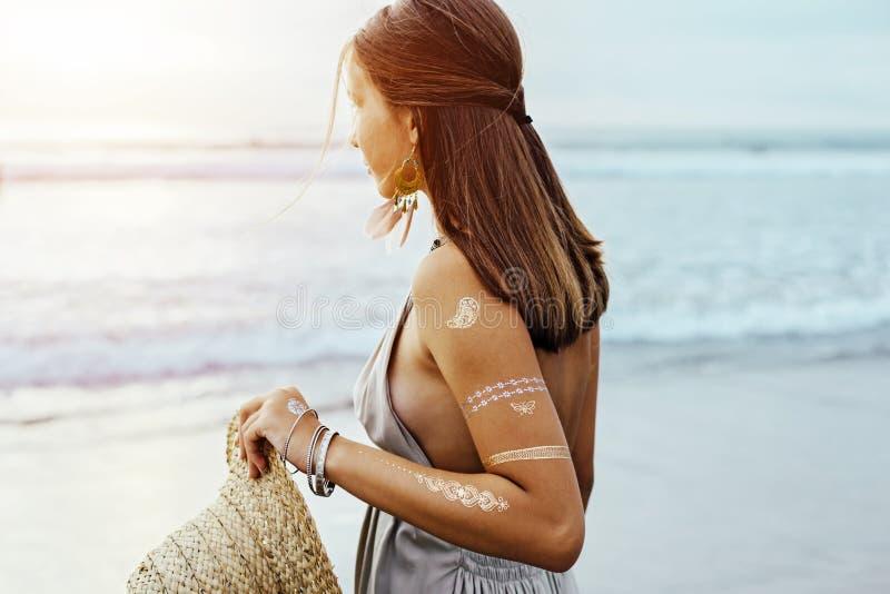 Junges Mädchen mit silbernem Tätowierungs- und bohoschmuck auf Sonnenuntergang stockfoto