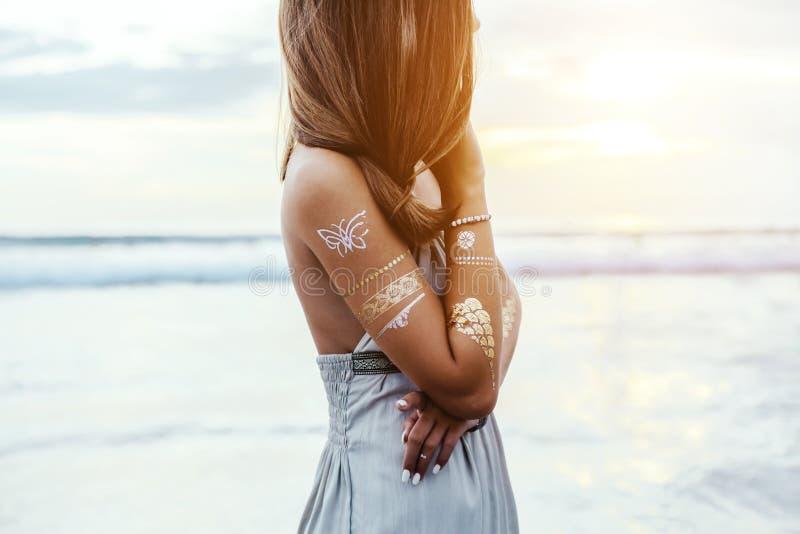 Junges Mädchen mit silbernem Tätowierungs- und bohoschmuck auf Sonnenuntergang lizenzfreie stockfotografie