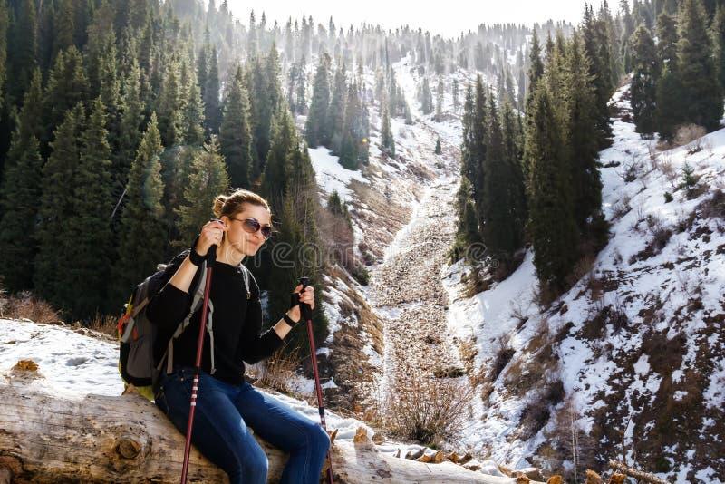 Junges Mädchen mit Trekking haftet das Stillstehen auf einem gefallenen Baum im Hintergrund von Schnee-mit einer Kappe bedeckten  stockfotografie