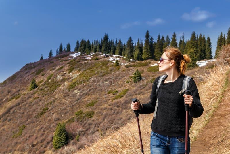 Junges Mädchen mit Trekkingsstöcken geht in Berge lizenzfreie stockfotos