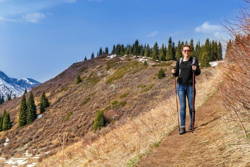Junges Mädchen mit Trekkingsstöcken geht entlang den Gebirgspfad stockbilder