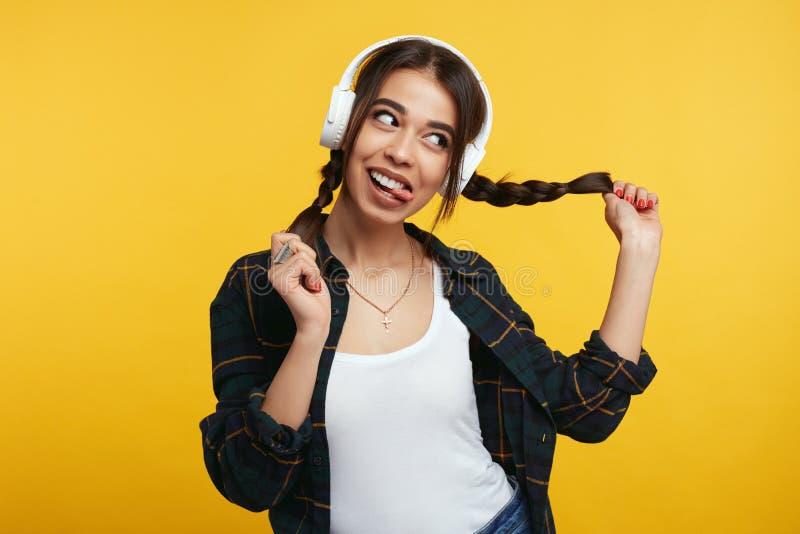 Junges Mädchen mit weißen Kopfhörern, hört Musik und fühlt sich froh und spielt mit ihren Pferdeschwänzen und weg schaut un stockbild