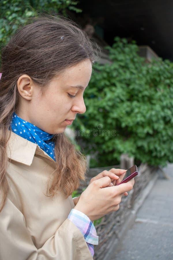 Junges Mädchen schaut in einem Smartphone, der in seinen Händen hält stockfotos