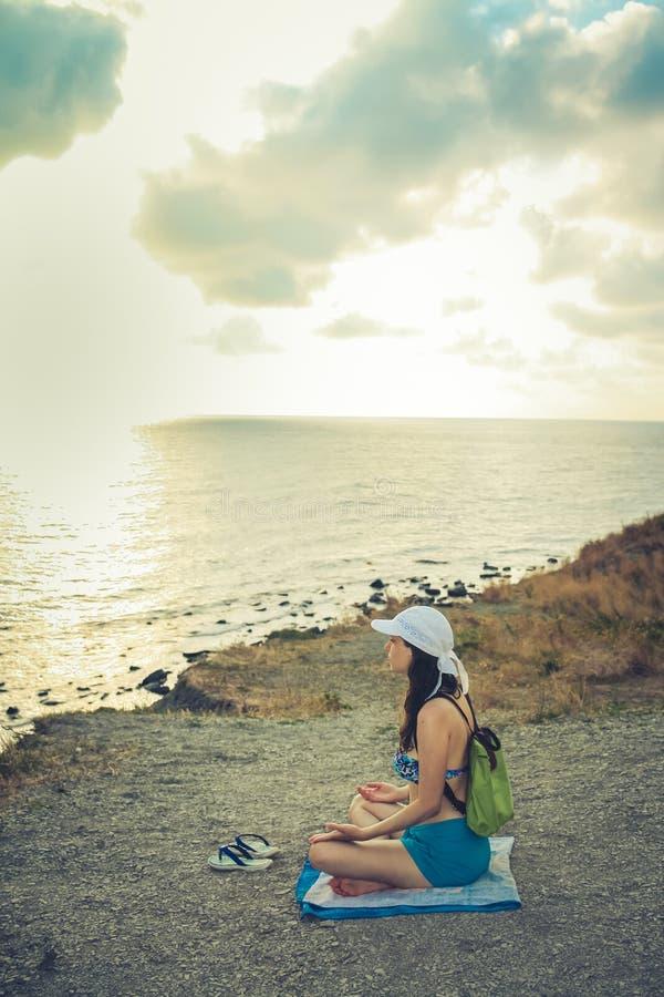 Junges Mädchen sitzt auf einer steinigen Seeküste und betrachtet Meer bei Sonnenuntergang Hintere Ansicht stockfotografie