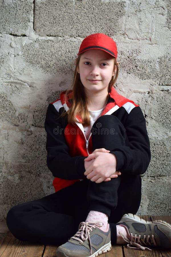 Junges M?dchen sitzt im schwarzen Sportanzug, in der roten Kappe und im L?cheln Konzeptportr?t eines angenehmen freundlichen gl?c stockbilder