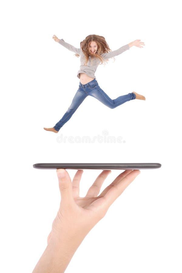 Junges Mädchen springen mit Tabletten-PC auf Leutehand stockfotografie