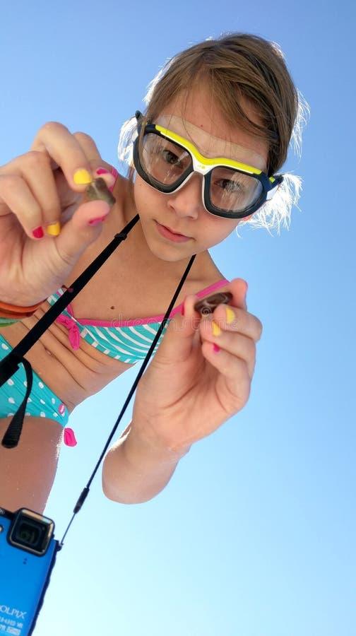 Junges Mädchen am Strand mit Kieseln lizenzfreie stockfotos