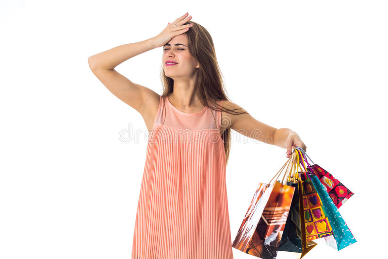 Junges Mädchen tat eine Hand hinter ihrem Kopf und hält die anderen verschiedenen Einkaufstaschen lokalisiert auf weißem Hintergr lizenzfreie stockfotografie