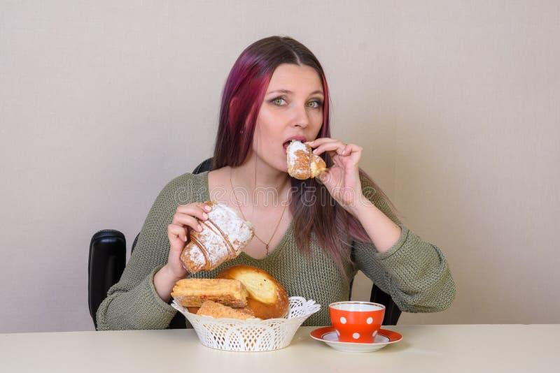 junges Mädchen am Tisch beißt eine Scheibe des Tees ab lizenzfreies stockbild