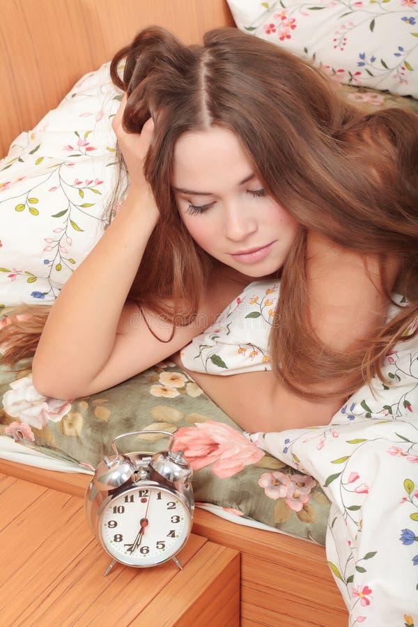 Junges Mädchen und Alarmuhr stockbild