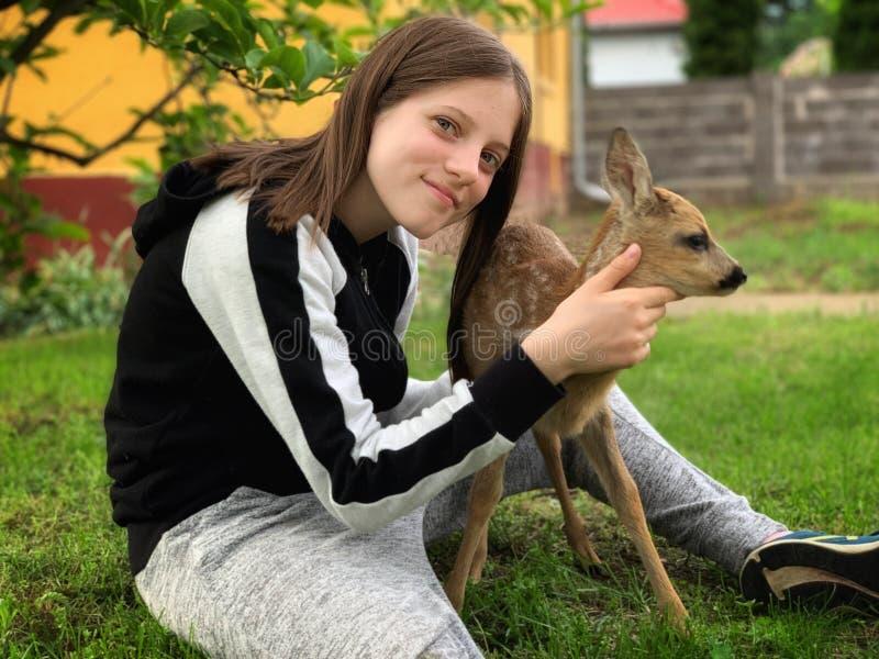 Junges Mädchen und ein kleines Rotwild stockfoto