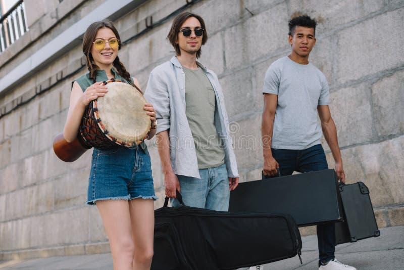 Junges Mädchen und gemischtrassige Männer, die Musikinstrumente auf sonnigem gehen und tragen lizenzfreies stockfoto