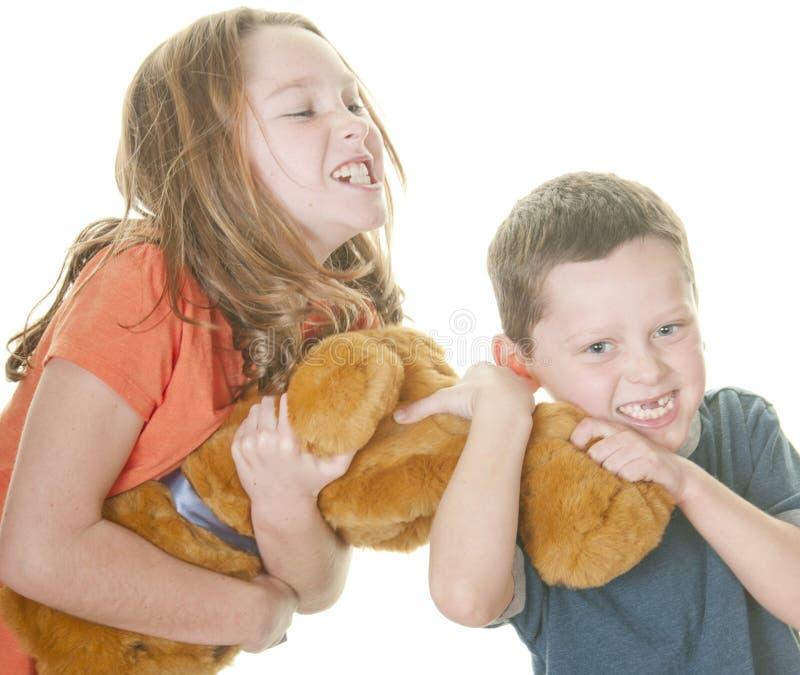 Junges Mädchen und Junge, die über Bären kämpft lizenzfreie stockbilder