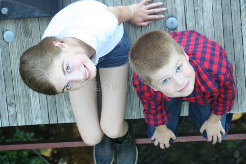 Junges Mädchen und Junge, die auf einer Brücke sitzt lizenzfreie stockfotos