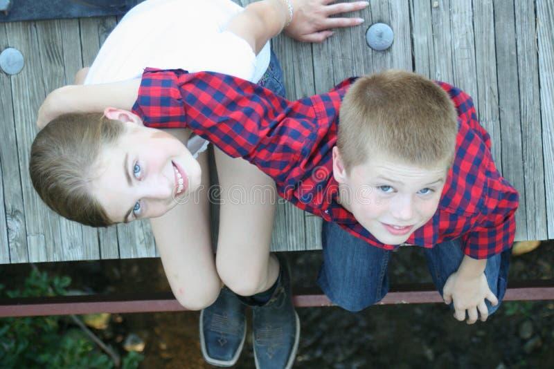 Junges Mädchen und Junge, die auf einer Brücke sitzt lizenzfreie stockbilder