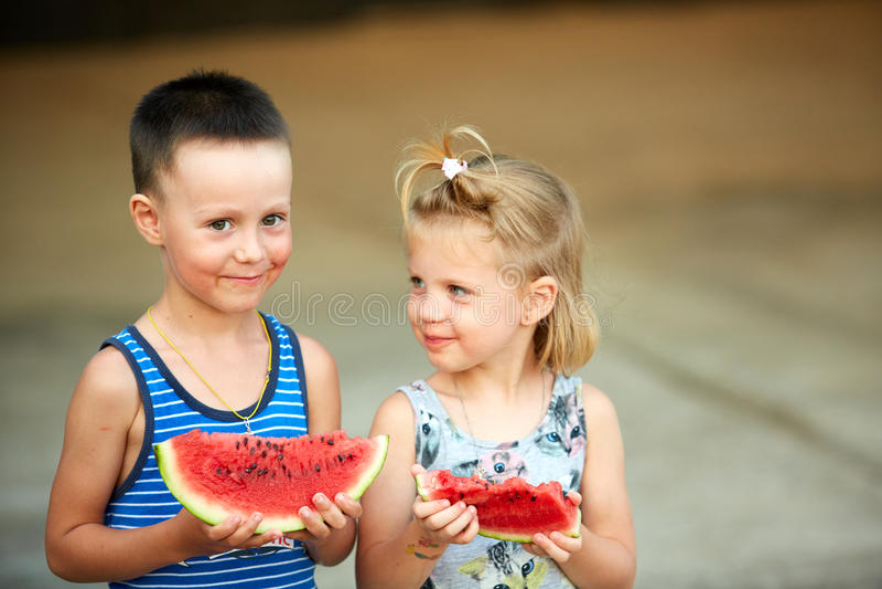 Junges Mädchen und Junge, die Wassermelone isst stockfoto