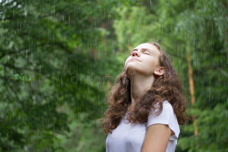 Junges M?dchen unter dem Regen in einem Sommerpark lizenzfreie stockfotos