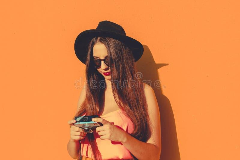 Junges Mädchen unter Verwendung einer Weinlesefotokamera, die moderne Sonnenbrille und einen schwarzen Hut trägt lizenzfreies stockfoto