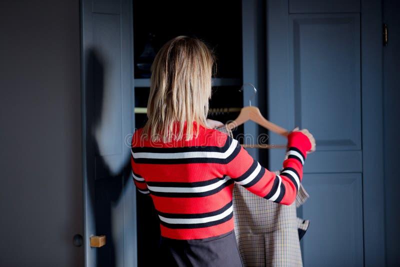 Junges Mädchen wählen ein Kleid zu Hause nahe Garderobe stockbild