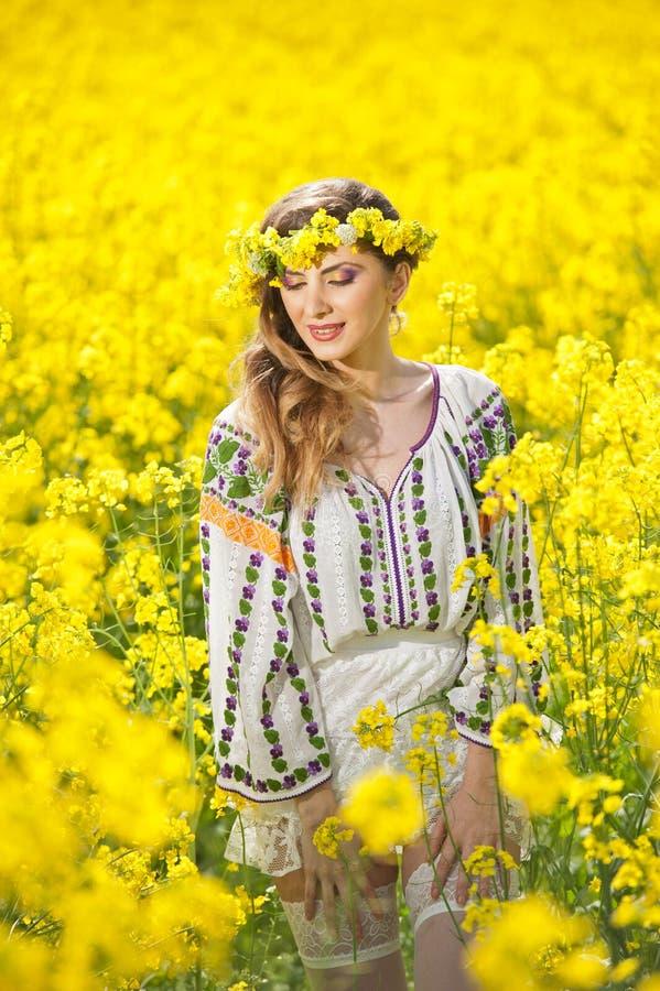 Junges Mädchen, welches die rumänische traditionelle Bluse aufwirft auf dem Canolagebiet, Außenaufnahme trägt Porträt der schönen lizenzfreies stockbild