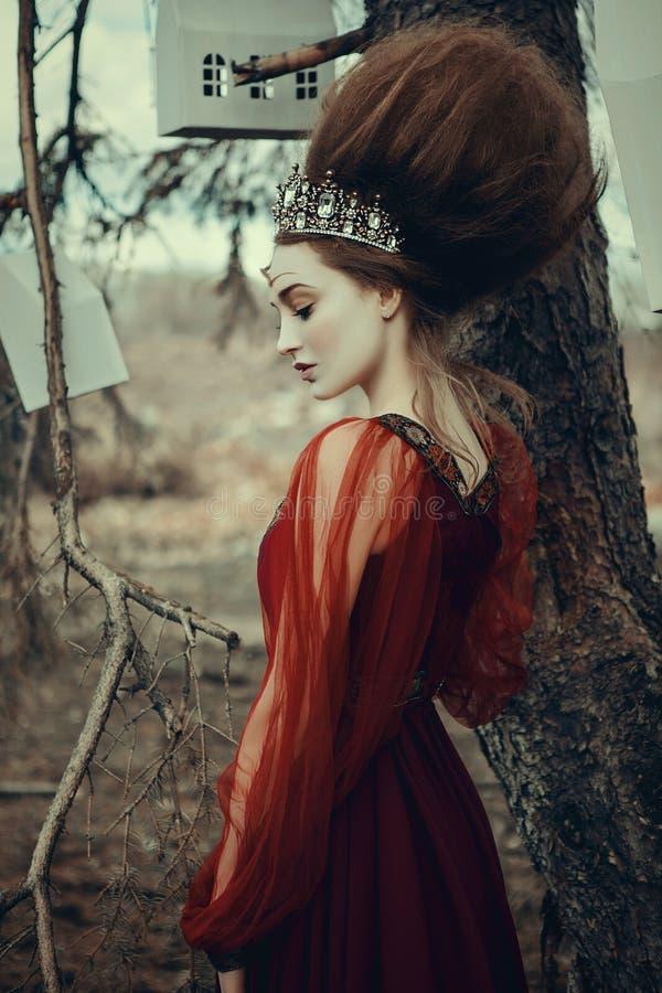 Junges Mädchen wirft in einem roten Kleid mit kreativer Frisur auf stockfotos