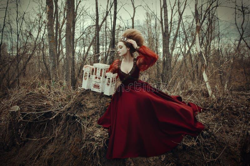 Junges Mädchen wirft in einem roten Kleid mit kreativer Frisur auf stockfotografie