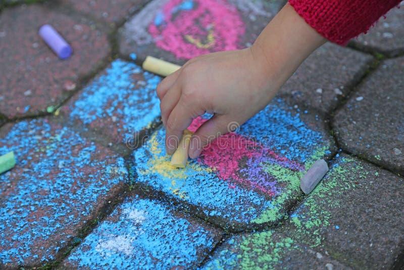 Junges Mädchen zeichnet mit den bunten Kreiden stockbilder
