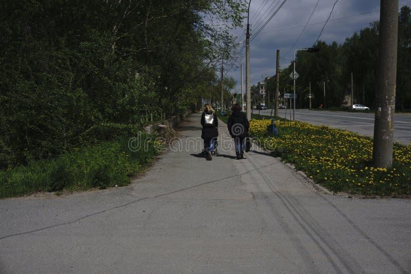 Junges Mädchen zwei, das zusammen geht zwei glückliche elegante Mädchen, die auf Frühling laufen, gehen, hintere Ansicht, Freunds lizenzfreie stockfotos