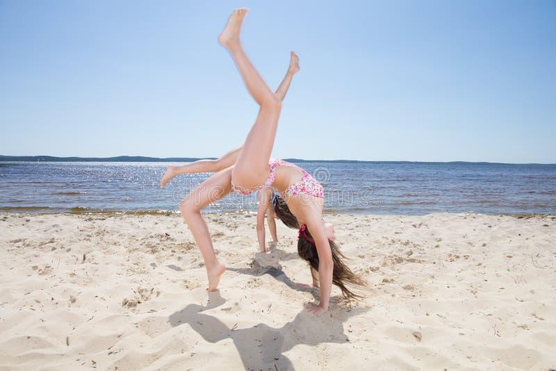 Junges Mädchenhandeln gymnastisch und Wagenrad auf dem Strand stockbild