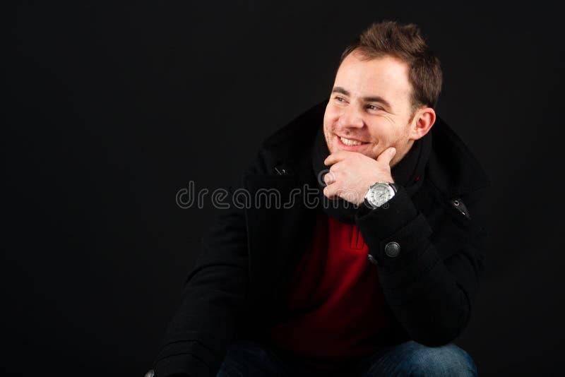 Junges männliches Baumuster, das einen Wintermantel lächelt und trägt lizenzfreie stockbilder