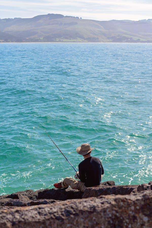 Junges männliches Fischen von den Wellenbrecher-Felsen an einem Jachthafen stockbild