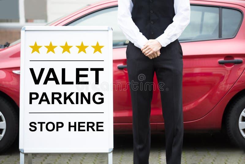 Junges männliches Kammerdiener-Standing Near Valet-Parkzeichen lizenzfreie stockfotos