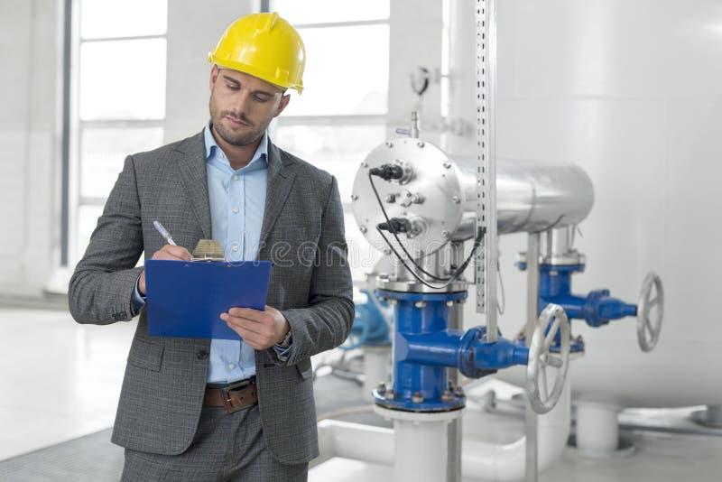 Junges männliches Managerschreiben auf Klemmbrett in der Industrie stockfoto