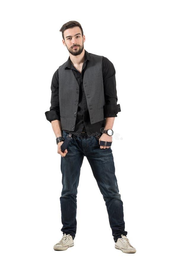 Junges männliches Mode-Modell, das seine Hosenträger betrachten Kamera hält stockfoto