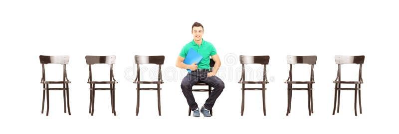 Junges männliches Sitzen auf einem Stuhl und Warteeinem Vorstellungsgespräch lizenzfreies stockbild