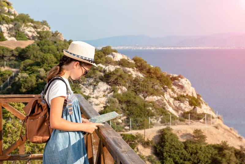Junges M?dchen, das Reisekarte in den Bergen nahe dem Meer betrachtet lizenzfreies stockbild