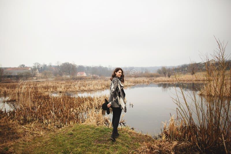 Junges M?dchen in der grauen Wolljacke und im L?cheln und in den Haltungen des schwarzen Hutes auf dem Ufer von einem See lizenzfreies stockfoto