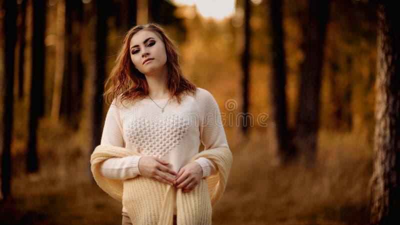Junges M?dchen in der hellen Kleidung gegen einen Hintergrund von Baumst?mmen im Herbstwald stockbilder