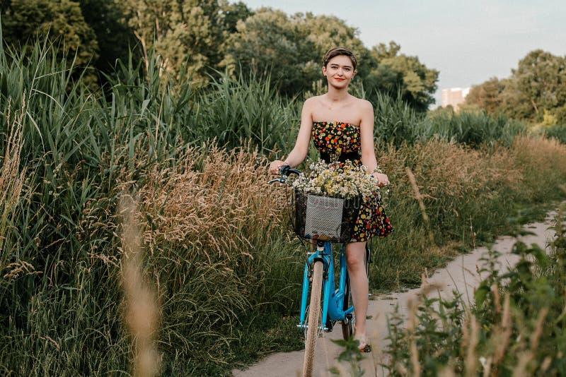 Junges M?dchen mit einem Fahrrad Sch?nheit und Blumen im Korb Gehen in die Natur Reise stockbilder