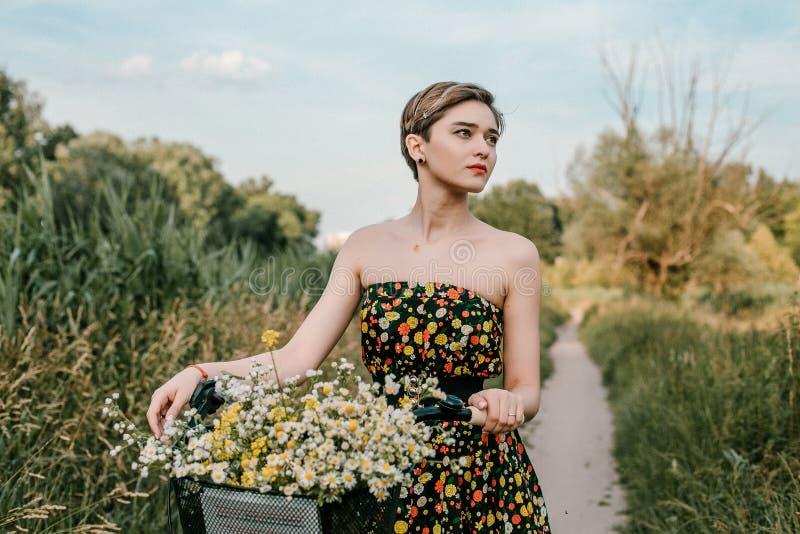 Junges M?dchen mit einem Fahrrad Sch?nheit und Blumen im Korb Gehen in die Natur Reise lizenzfreie stockfotografie