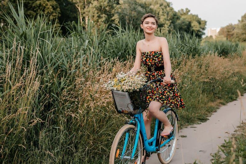 Junges M?dchen mit einem Fahrrad Sch?nheit und Blumen im Korb Gehen in die Natur Reise stockfoto