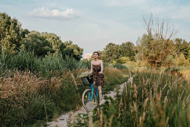 Junges M?dchen mit einem Fahrrad Sch?nheit und Blumen im Korb Gehen in die Natur Reise lizenzfreies stockbild