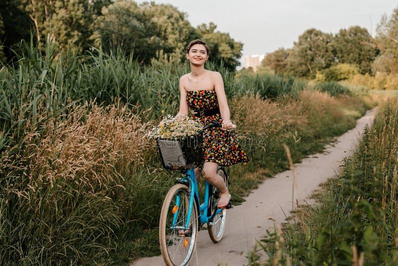 Junges M?dchen mit einem Fahrrad Sch?nheit und Blumen im Korb Gehen in die Natur Reise lizenzfreie stockbilder