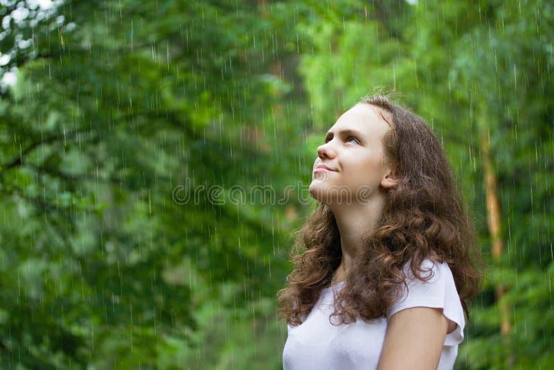 Junges M?dchen unter dem Regen in einem Sommerpark lizenzfreie stockbilder