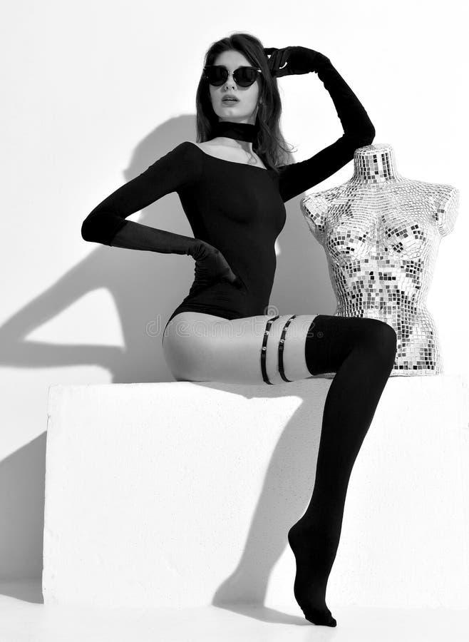 Junges Mode Brunettemädchen in der Sonnenbrille mit modernem Statuenmann lizenzfreies stockfoto