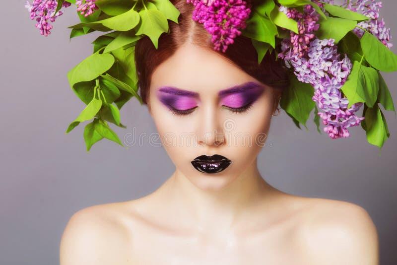 Junges Modell mit kreativem Make-up auf ihrem Gesicht und Kopfschmuck von Blumen stockbilder